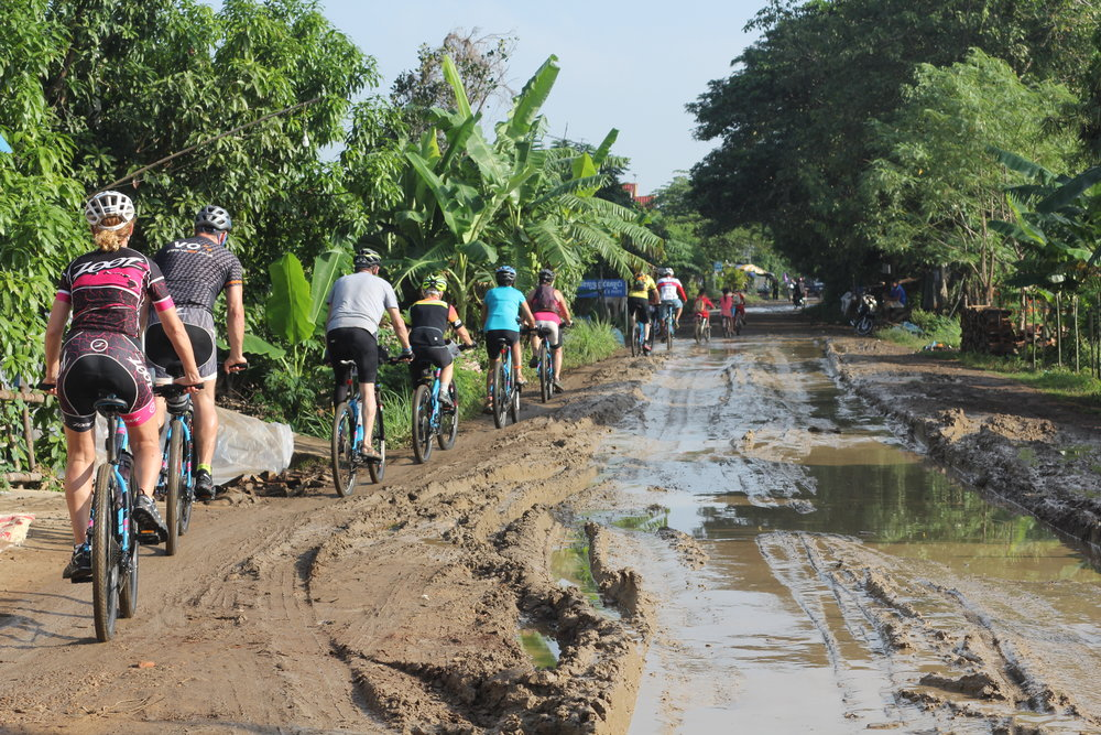 group-of-cylists-on-cycle-adventure-cycling-on-muddy-path-in-south-east-asia-vitenam-to-cambodia-with-360-expeditions.JPG