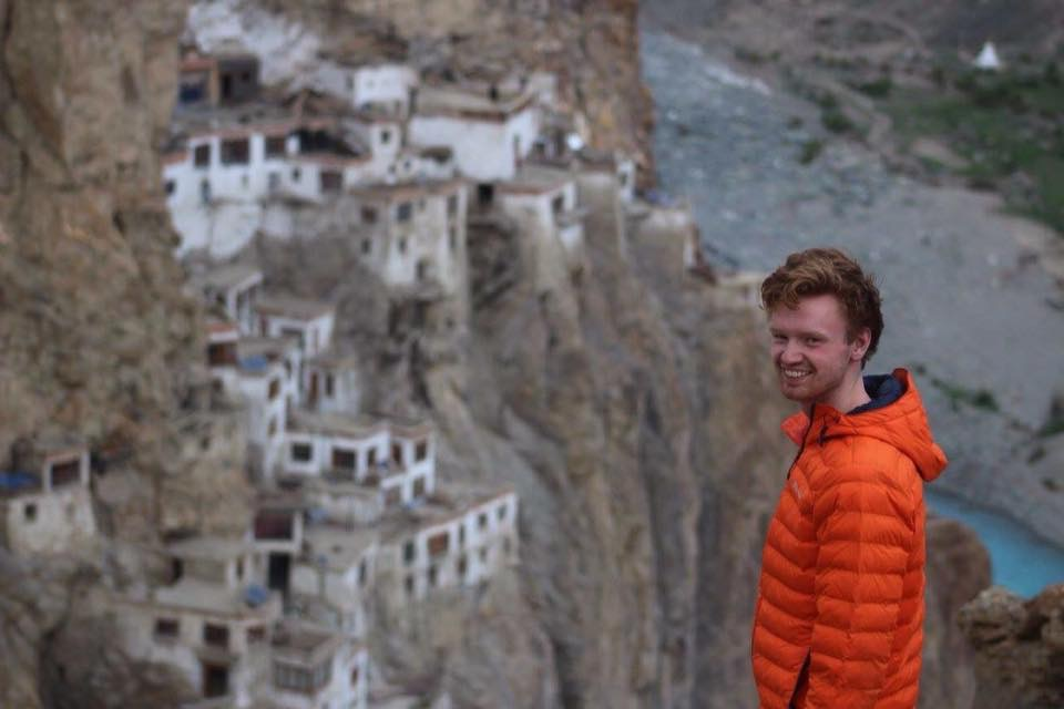 Image of Jago standing in mountains wearing orange jacket and smiling