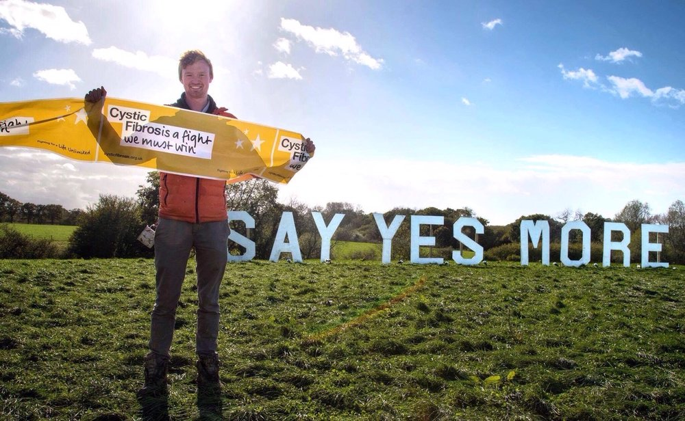 An image of Jago at Yestival 2018 standing in front of the Say Yes More sign in the field of dreams