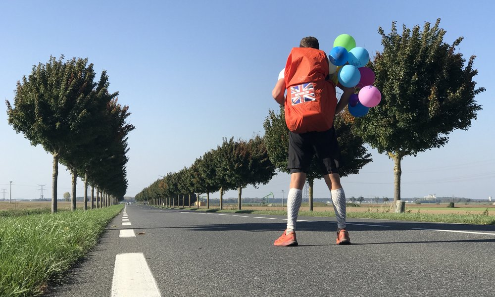 Image of Dan standing with his back to the camera, in a very straight road looking into the distance- wearing a bunch of colourful balloons on his back pack