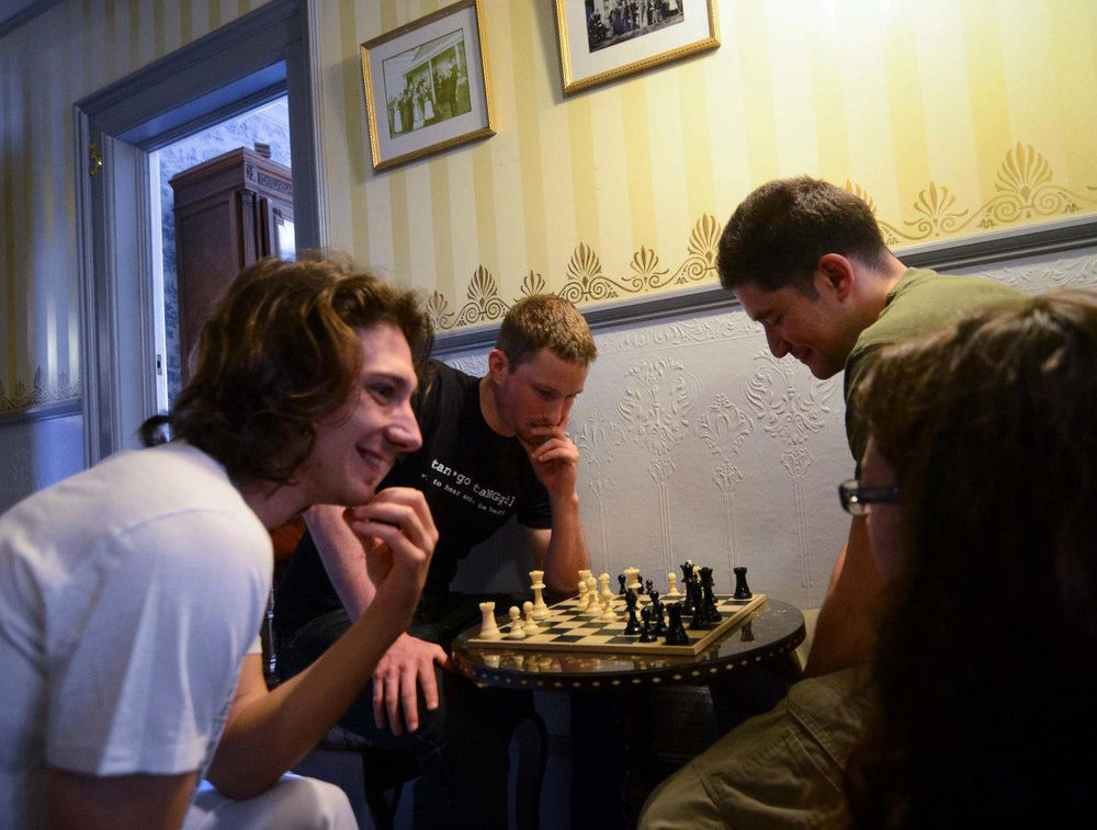 Dancer-organizers playing chess at Weller House Inn at the Tango Slumber Party in 2013. Photo by SubbusClicks.
