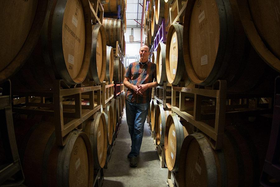 Winemaker Stephen Dooley between rows of stacked barrels.