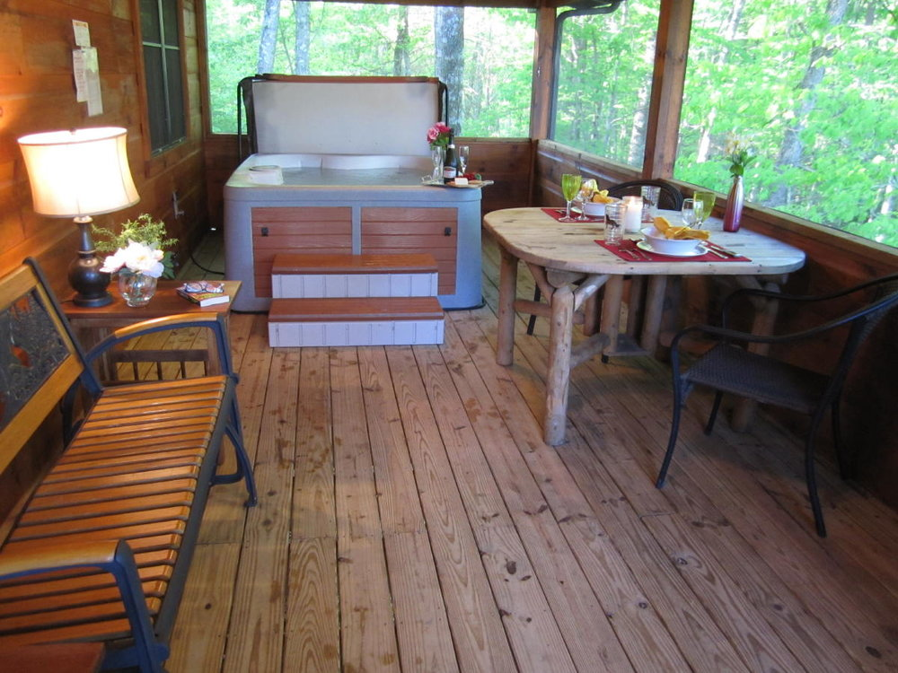 Outdoor dining and hot tub at Arabian Nights cabin.