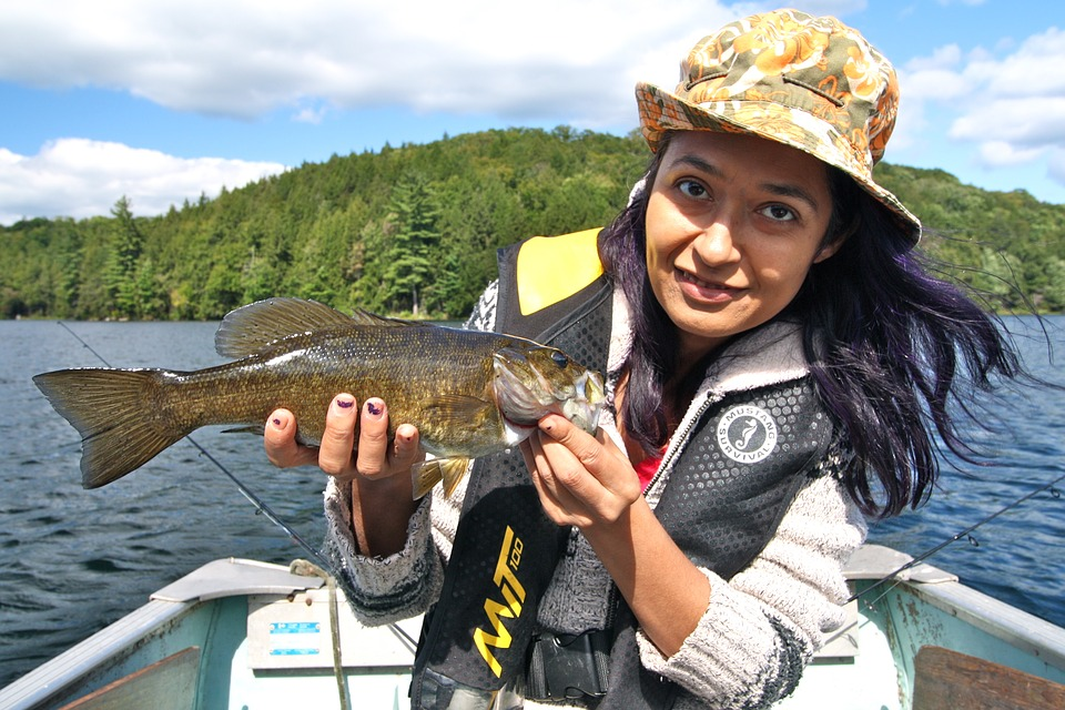 woman holding a smallmouth bass while fishing from a boat