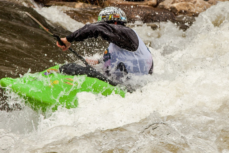 whitewater rafter paddling through rapids