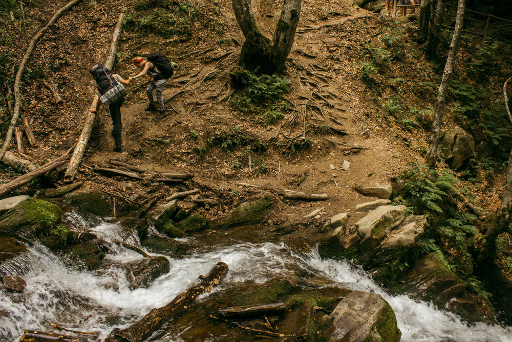 two hikers climbing up a hill near a creek