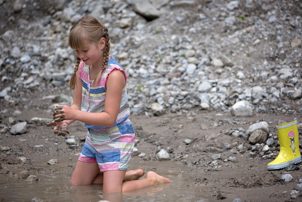 girl playing in the mud on a river bank while on vacation