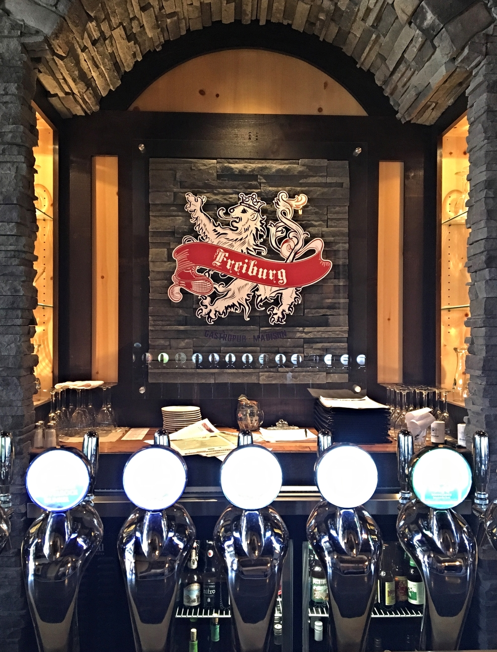 Fine masonry surrounding the Freiburg logo illuminated by custom beer taps from Italy.                       Photo by Epicurean Chronicles