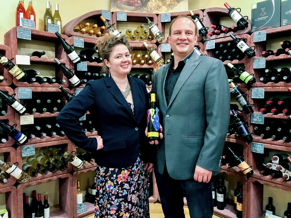 Chef Kristin Williams and vomFass Owner Justin Gibson holding a bottle of HandPrint Merlot