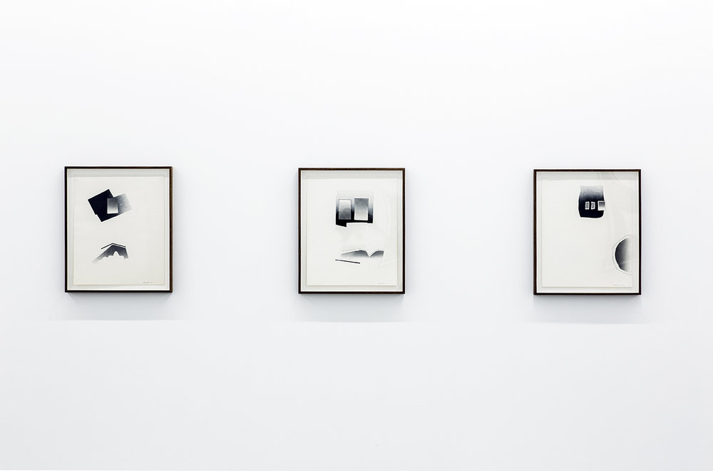Installation view of three of Deborah Remington's works on paper. Compositions of tonal grey and black shapes resembling mirrors floating above more organic abstract forms on a blank background.