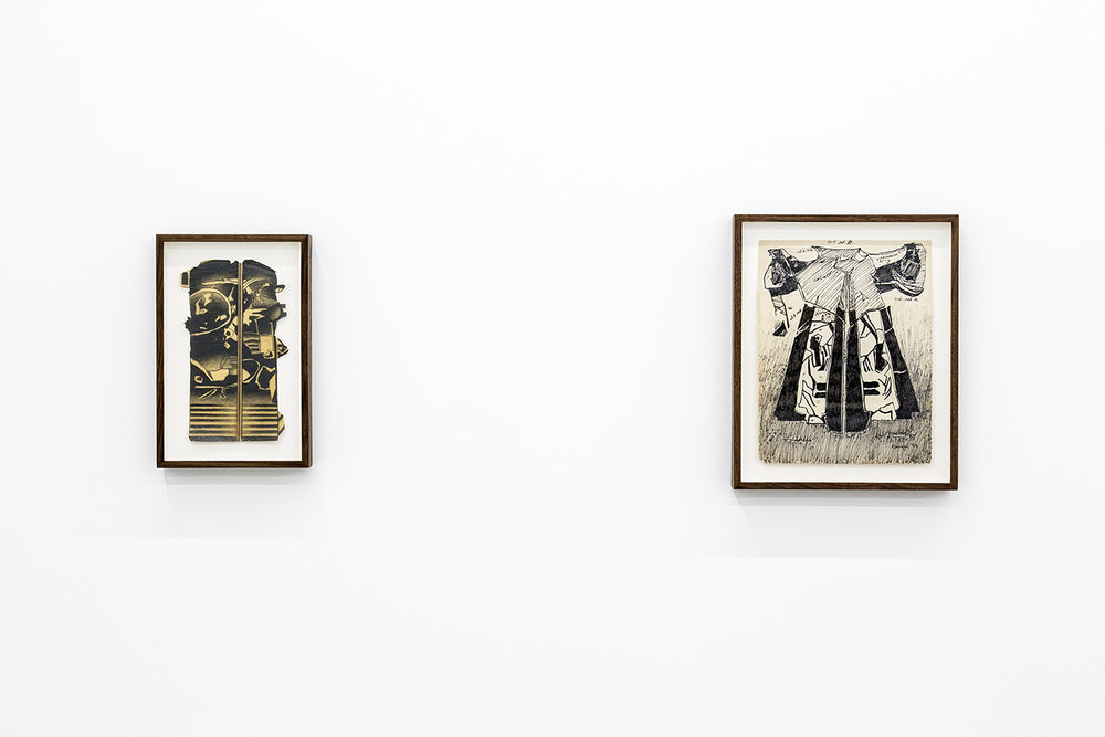 Installation view of two of Deborah Remington's works on paper. Semi-symmetrical abstract compositions resembling shields and armor built up of forms that are organic yet machine-like.
