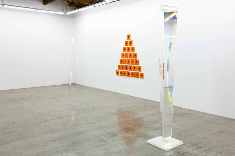 Installation view of Charles Ross' Solar Burns and Prisms, depicting a pyramid of orange square canvases with burns and a water filled prism.