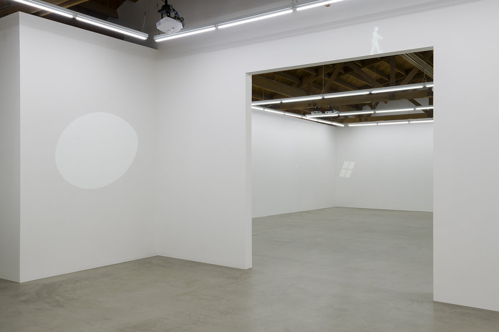 Installation view of Tom Friedman's Projections for Well-Lit Spaces; Guardian, a small man walking above a doorway, a gigantic egg in rotation, and UFO, which begins as a four-pane window into a UFO
