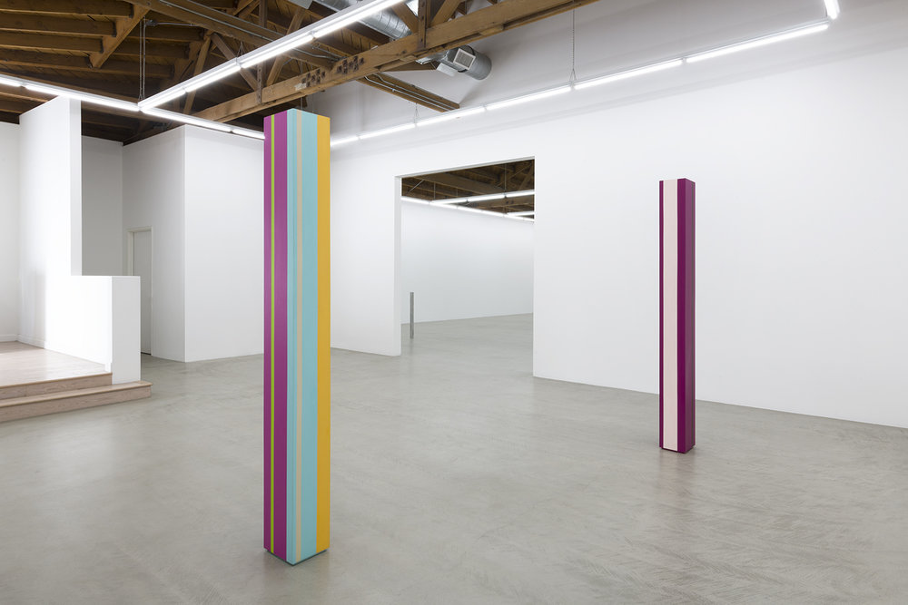 A back installation view of the two Anne Truitt sculptures in the show, showing vertical stripes of magenta, teal, yellow and pink
