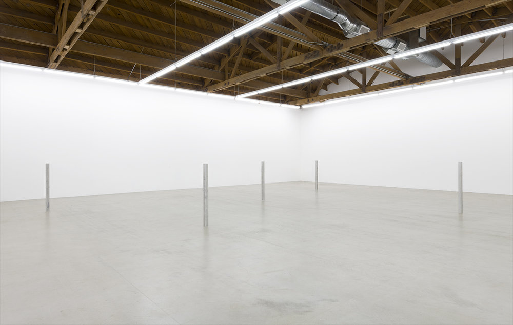 Installation image of all five aluminum and steel cast sculptures standing erect methodically placed within the gallery