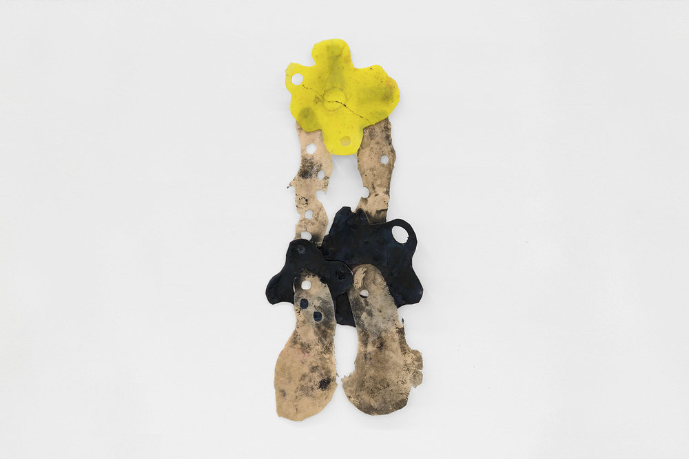 Copy of Sara Gernsbacher's abstract sculpture made of silicone and acrylic paint resembling yellow flower with flesh-toned legs on either side intertwined in black flowers hanging against a white wall