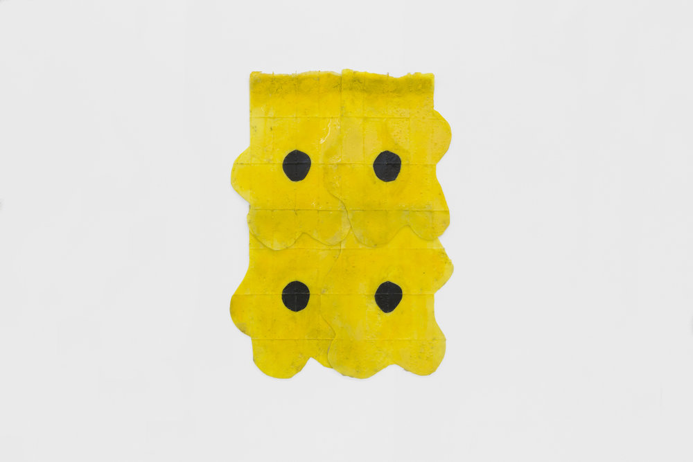 Copy of Sara Gernsbacher's abstract sculpture made of silicone and acrylic paint resembling four glossy grid textured bright yellow flowers with black centers in two stacked rows hanging against a white wall