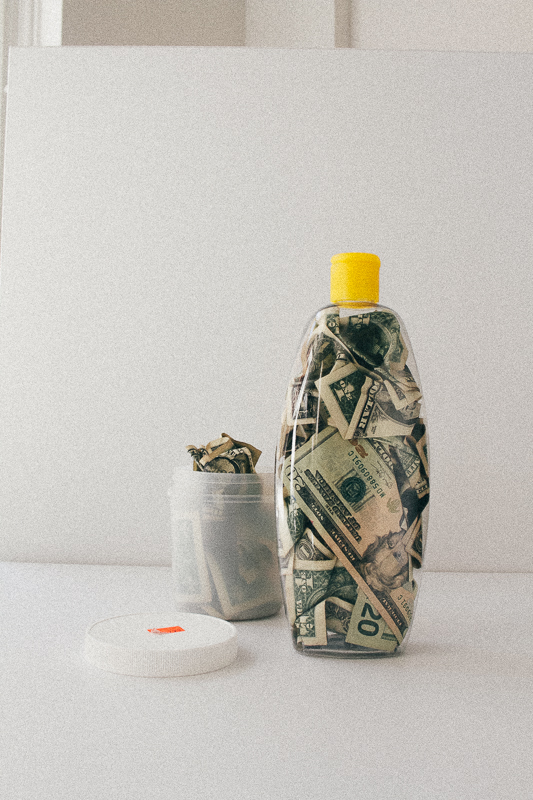 An empty edge control tub and baby shampoo bottle filled with money.