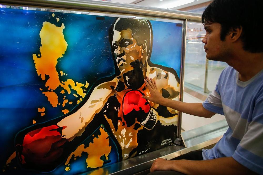 Filipino boxing aficionado Marco Jose Revilla pays respect to an artwork by Monica Jane Valerio depicting Muhammad Ali inside the 'Ali Mall', the country's first mall named after the legendary boxing champion displayed in Quezon City, northeast of Manila, Philippines, on June 4. (Mark R. Cristino/EPA)