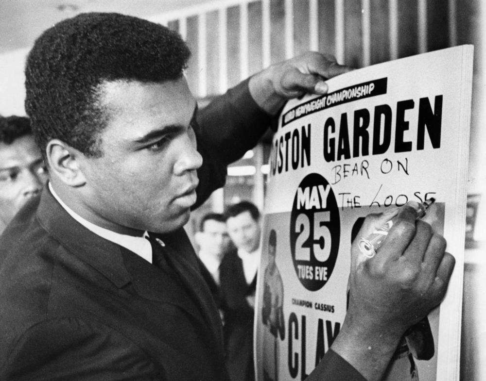 "Heavyweight boxing champion Cassius Clay arrived at his Boston training camp to launch final preparations for the title rematch with Sonny Liston. The champion mugged a bit for the benefit of the patrons of his training site at the Schine Inn at Chiopee, and scrawled on posters advertising the fight; ""Bear On The Loose."" Clay's pet name for Liston is ""The Bear."" (Associated Press)"