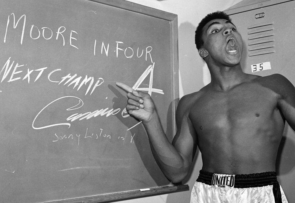 Young heavyweight boxer Cassius Clay, who later changed his name to Muhammad Ali, points to a sign he wrote on a chalk board on Nov. 15, 1962 in his dressing room before his fight against Archie Moore in Los Angeles. (Harold P. Matosian/Associated Press)
