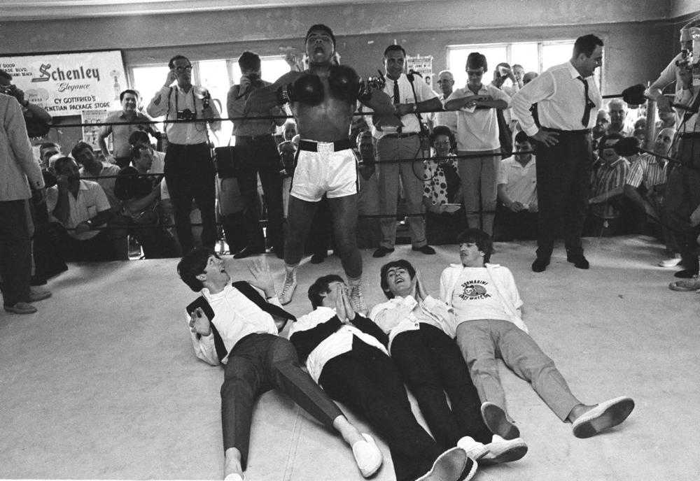 Muhammad Ali, or Cassius Clay at the time, beats his chest in triumph after toppling Britain's Beatles at his training camp in Miami Beach, Fla., on Feb. 18, 1964. The Beatles, left to right: Paul McCartney; John Lennon; George Harrison and Ringo Starr, were on Holiday in the resort after their American tour. (Associated Press)