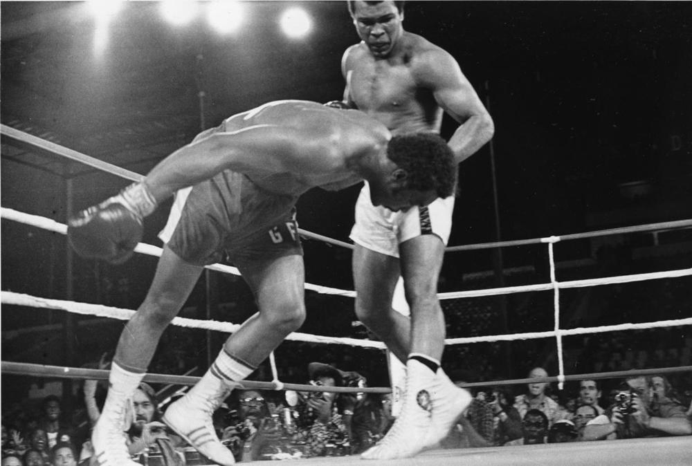 Muhammad Ali watches as defending world champion George Foreman goes down to the canvas in the eighth round of their WBA/WBC championship match in Kinshasa, Zaire on Oct. 30, 1974. (Associated Press)