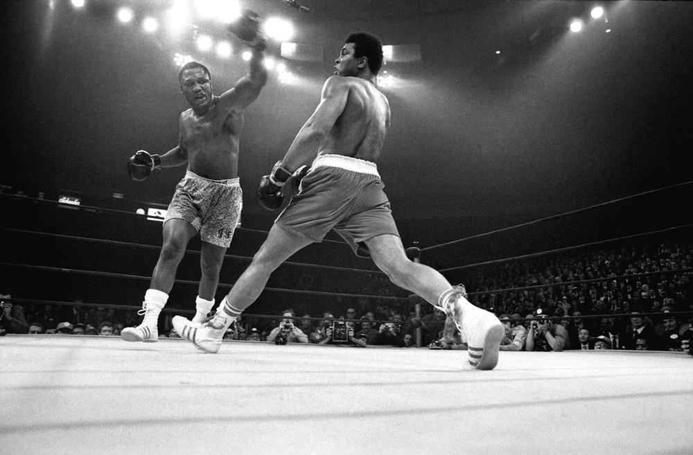 "Muhammad Ali evades a left from Joe Frazier during their title bout, the ""Fight of the Century,"" at Madison Square Garden in New York, on March 8, 1971. Five years after being stripped of his titles for refusing to register for the draft, Ali suffered the first defeat of his career here. Ali died in Phoenix on June 3. (Larry C. Morris/The New York Times)"