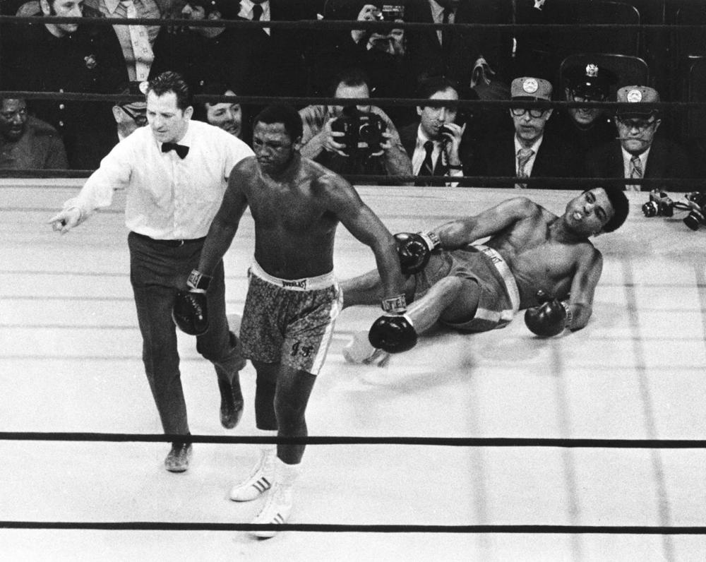 Joe Frazier is directed to a corner by referee Arthur Marcante after Frazier knocked down Muhammad Ali during the 15th round of the title bout in Madison Square Garden in New York on March 8, 1971. Frazier won the bout over Ali by decision. (Associated Press)