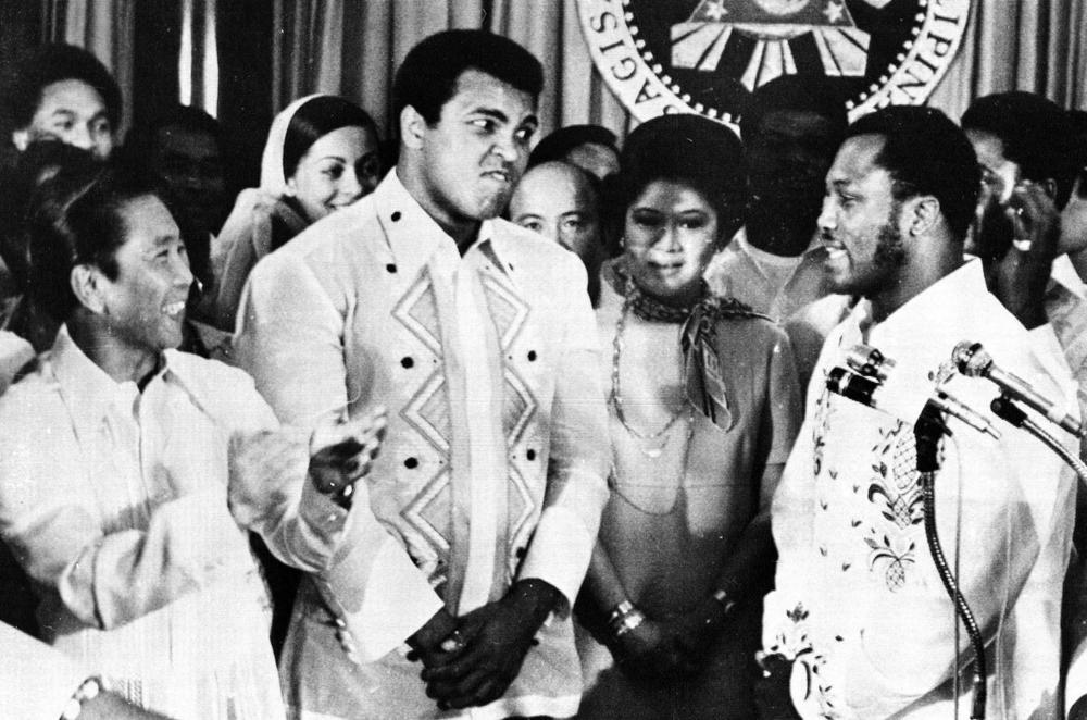 Philippines President Ferdinand Marcos, left, applauds as challenger Joe Frazier, right, makes some remarks about world champion Muhammad Ali, second from left, during their call on Marcos at the Malacanang Palace in Manila, Philippines on Sept. 18, 1975. (Jess Tan/Associated Press)