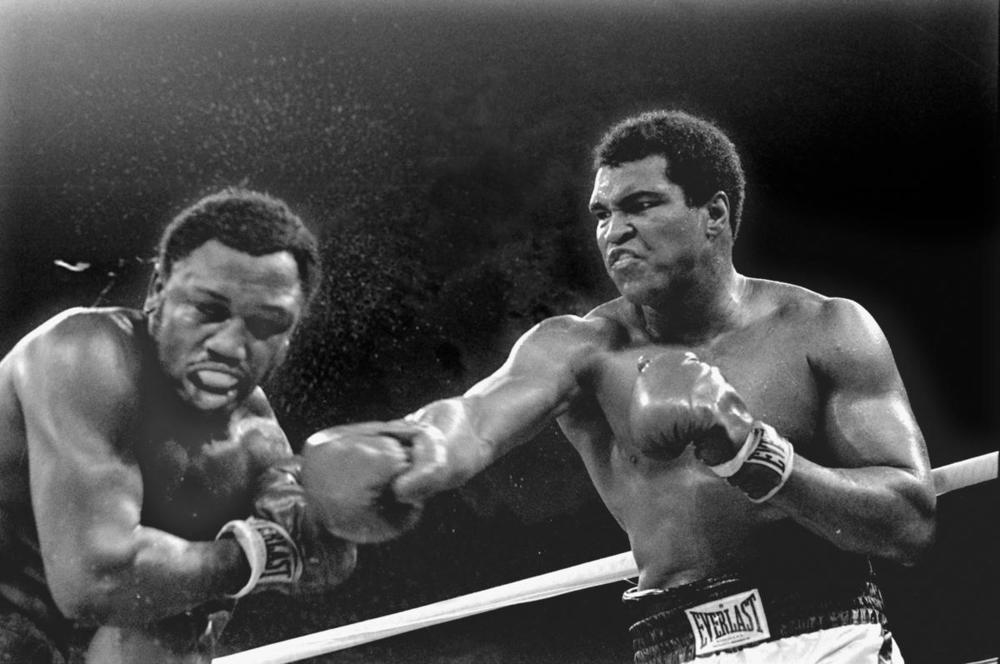 Spray flies from the head of challenger Joe Frazier as heavyweight champion Muhammad Ali connects with a right in the ninth round of their title fight in Manila, Philippines on Oct. 1, 1975. (Mitsunori Chigita/Associated Press)
