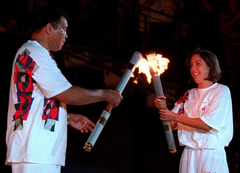 American swimmer Janet Evans passes the Olympic flame to Muhammad Ali during the 1996 Summer Olympic Games Opening Ceremony in Atlanta on July 19, 1996. (Michael Probst/Associated Press)