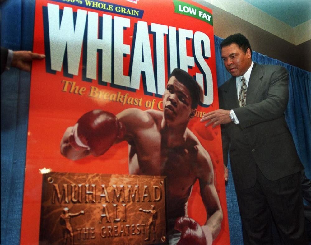 Muhammad Ali, reknown as 'The Greatest' fighter of all times, poses next to a Wheaties 'The Breakfast of Champions' poster during the unveiling of the 75th Anniversary cereal box in his honor in New York, on Feb. 4, 1999. 'Muhammad Ali is quite possibly the most recognized sports figure of our time,' said Wheaties market manager Jim Murphy. 'That's why we are especially proud to recognize him on our box during our 75th anniversary celebration.' (Bebeto Matthews/Associated Press)