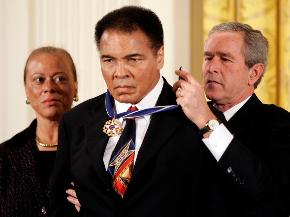 President George W. Bush awards boxing legend Muhammad Ali with the Presidential Medal of Freedom, as Ali's wife Lonnie watches, during a ceremony in the East Room of the White House in Washington on s Nov. 9, 2005. (Kevin Lamarque/Reuters)