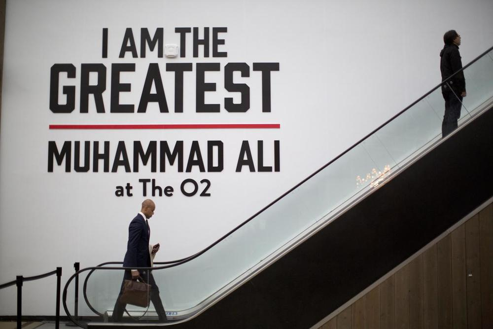 "Men pass a large sign by an escalator near the entrance of the ""I Am The Greatest, Muhammad Ali"" exhibition at the O2 arena, which hosts high profile boxing fights in London, on June 4. Ali, the magnificent heavyweight champion whose fast fists and irrepressible personality transcended sports and captivated the world, died according to a statement released Friday by his family. He was 74. (Matt Dunham/Associated Press)"