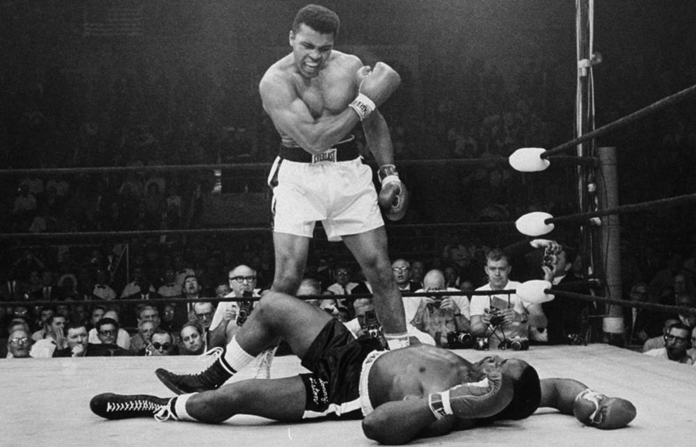 Heavyweight boxing champion Muhammad Ali stands over fallen challenger Sonny Liston in Lewiston, Me., on May 25, 1965. (John Rooney/Associated Press )