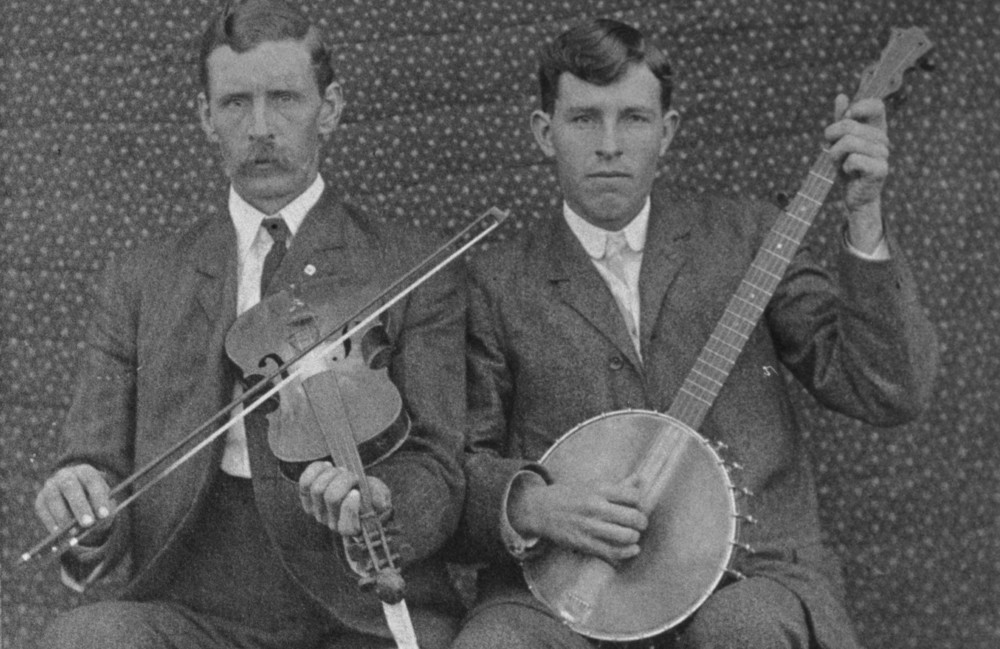 Josh and Henry Reed, ca. 1903. Henry Reed, age 19, plays banjo and his older brother Josh plays fiddle. Photograph from the collection of James Reed, reproduced with permission.