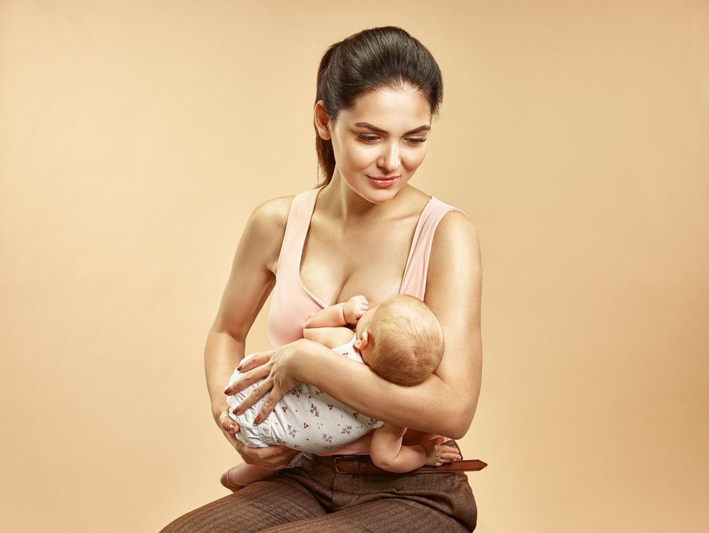 woman breastfeeding  baby sitting on  chair.