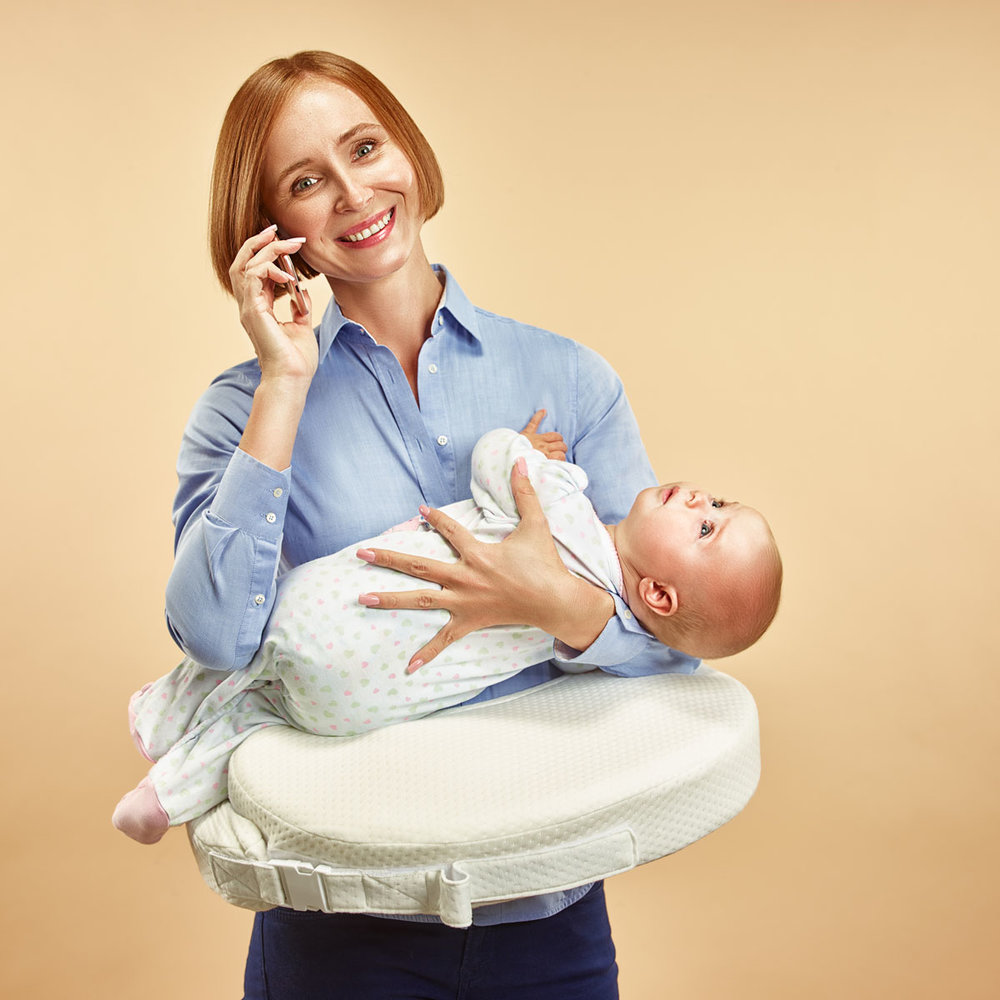 woman holds  baby in her arms using  special pillow. Talking on