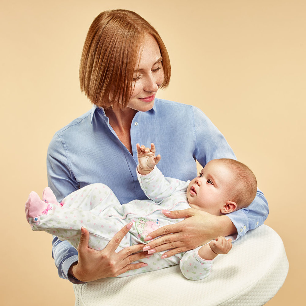 woman holds  baby in her arms using  special pillow.