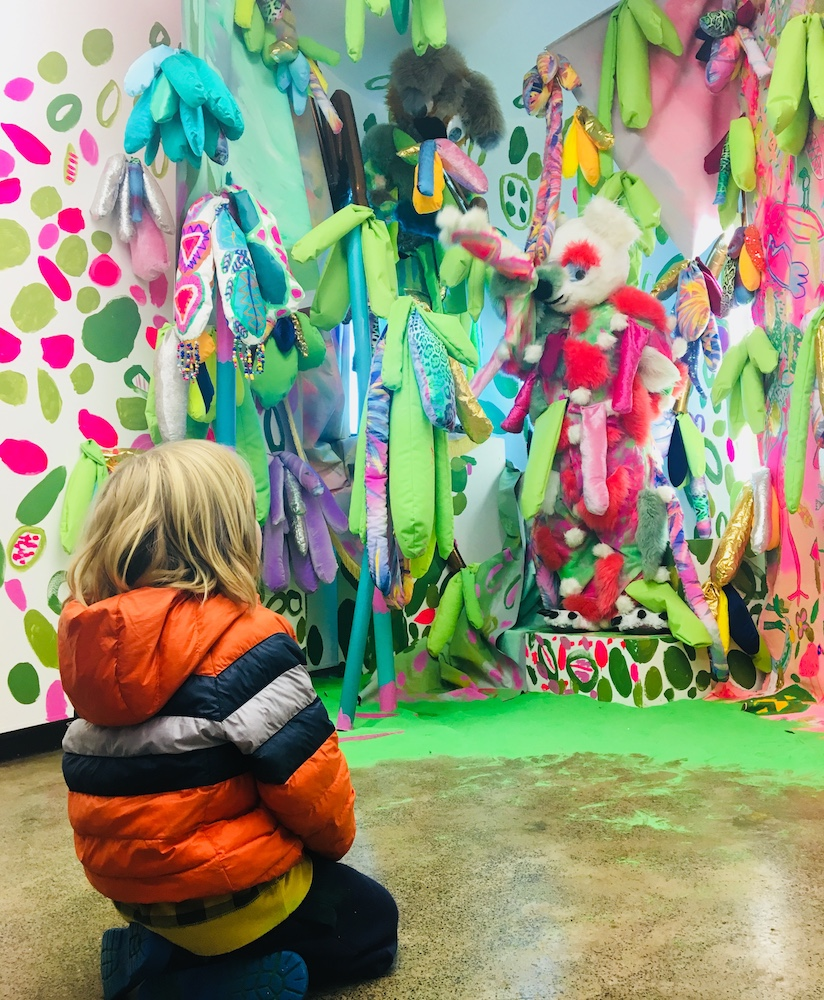 A child enjoying Emily Crockford and Rosie Deacon's installation,  Tree Bear Punk Queens of the Desert,  June 2018 ,  mixed media painting installation for Paired at Firstdraft, curated by Harriet Body