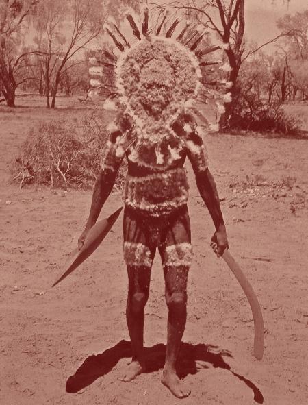 Totem du chat sauvage. Ultime photo de cette parure, disparue à jamais. Les plumes rouges sont celles du cacatoès. Dans la main droite, un propulseur pour longues lances de trois mètres, et dans la main gauche, un boomerang.