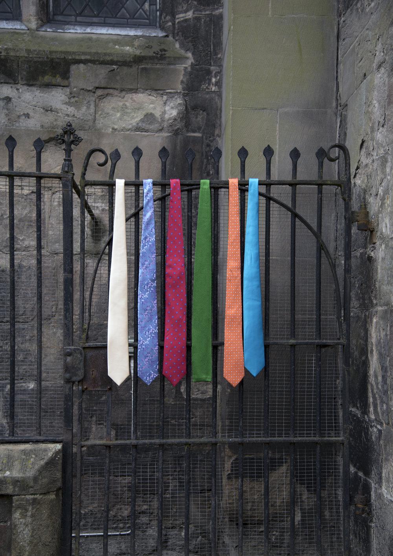 Row of colourful men's ties haning off railings in Hereford.jpg