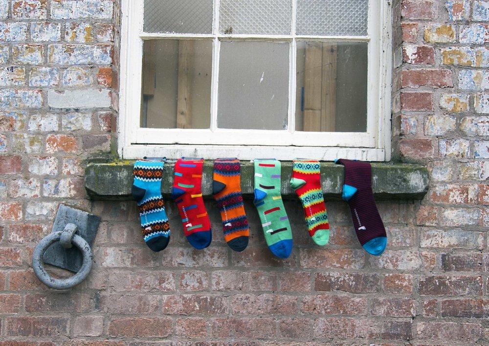 Line of coloured men's socks on windowsill Hereford.jpg