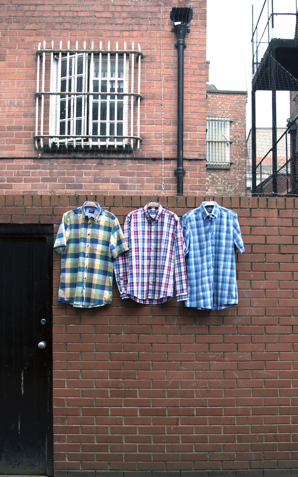 Row of short sleeved check shirts hanging on wall in Hereford.jpg