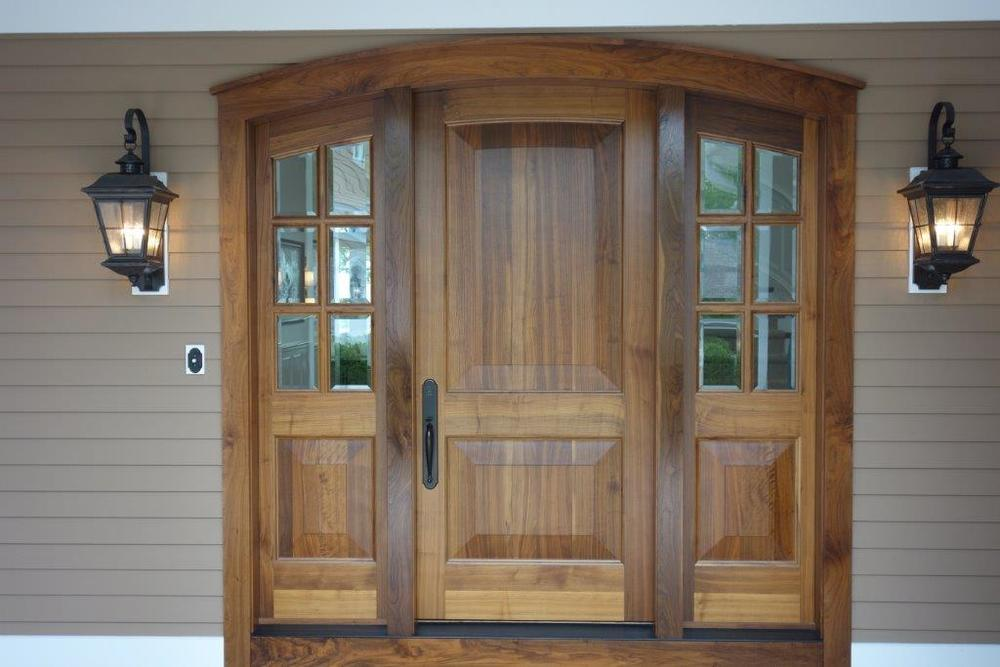 Raised panel black walnut entry door with beveled glass side lites.