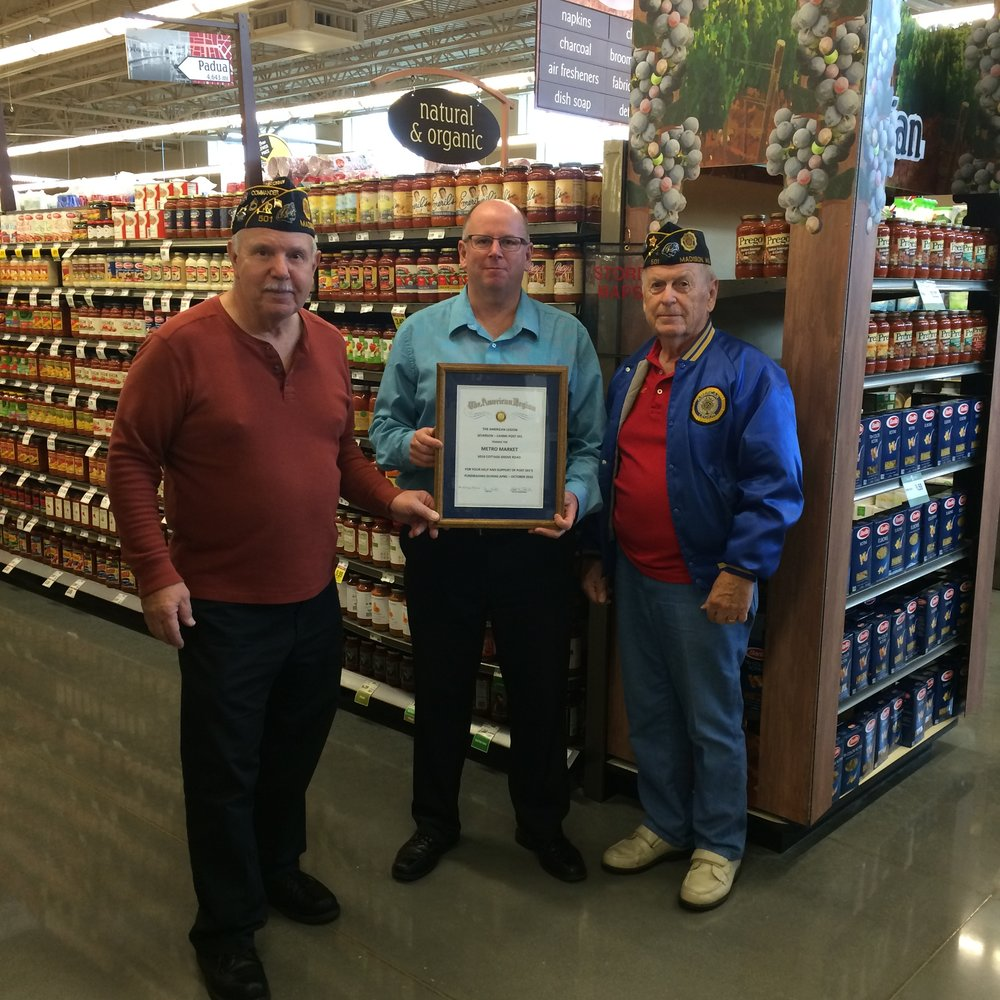 Certificate of Appreciation is presented to Tim Smits, Store Mgr., Metro Market, for their support of the Am. Legion Post 501 fund raising Brat Fests, by Post 501 Cdr, Tom Stolarczyk, and Phil Ingwell, Post 501 Finance Officer.