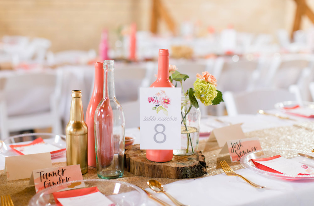 centerpieces, table numbers, and place cards for coral and gold wedding