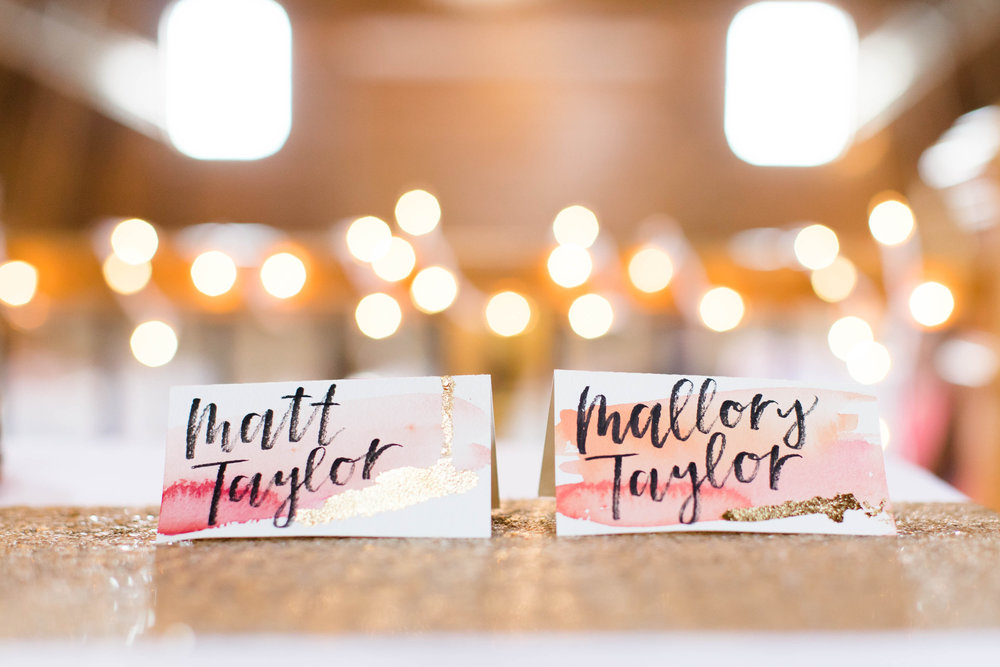 custom place cards with brush lettering calligraphy, coral watercolor paint, and gold accents