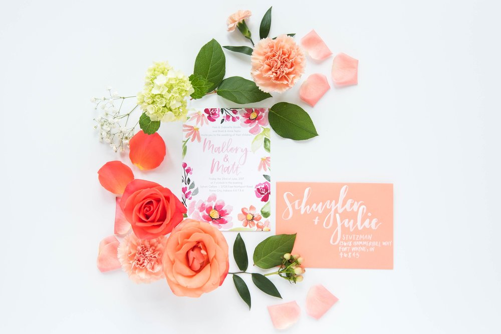 Colorful custom watercolor wedding invitations with white brush calligraphy for addresses